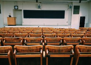 rows of chairs facing stage with podium and blackboard for Freshers' article