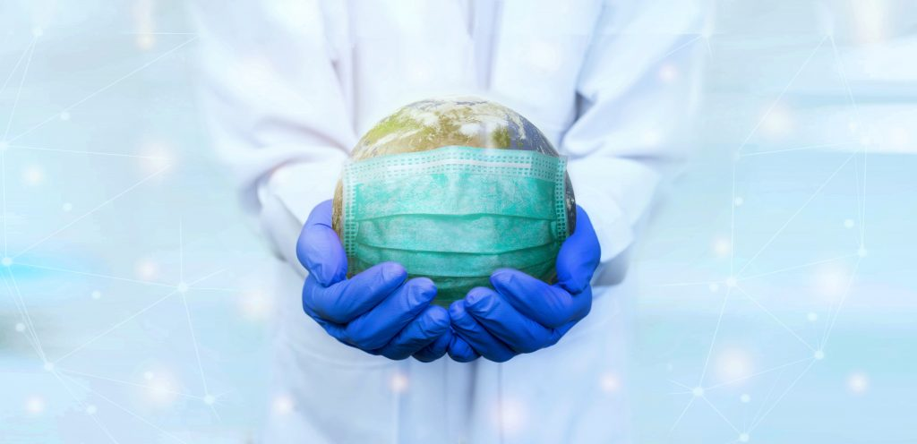 The World wearing a face mask sitting in the hands of a doctor/scientist to potray an image of the Covid-19 Pandemic
