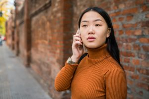 Young Asian woman talking on the phone outdoors in the street - for worried about friend on social media article