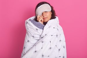 Close up portrait of brunette woman peeping from sleeping mask, wearing white blanket.  For unhealthy during lockdown article