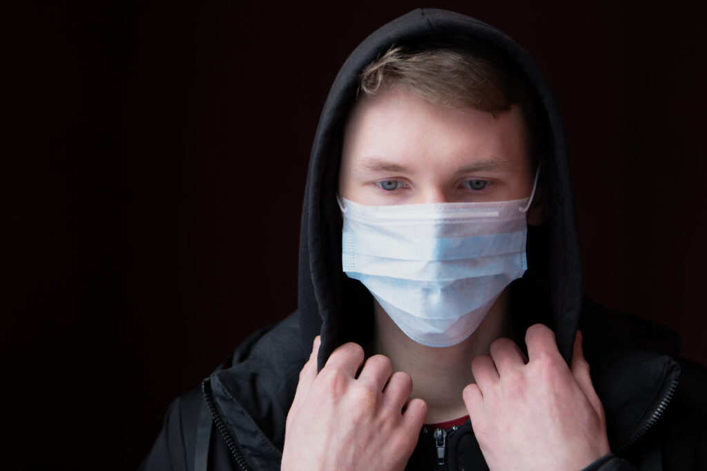 Sad, blue-eyed young man has protected himself from the coronavirus with a medical mask, and is looking down as he adjusts the hood of his jacket for Grab the Meic Fed up of Covid article.