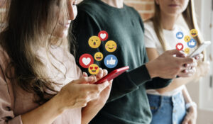 Three people on phones with emojis coming out of screen to signify likes etc. For online safety article