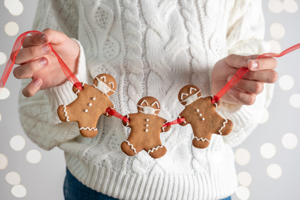 Person holding a row of christmas gingerbread men with a masks for latest Covid-19 rules article