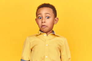 Young boy in yellow shirt recoiling with shock on his face. For online safety article