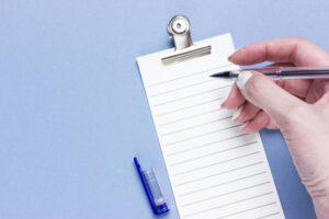 Ruled paper with hand holding pen ready to write