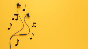 pair of bud earphones on yellow background with musical notes around them for remote learning tips article