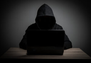 Shadowy figure on a computer for fake news blog
