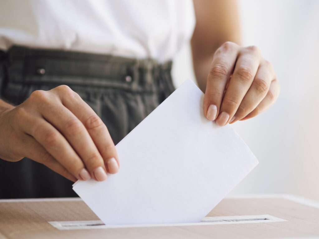 Woman's hands placing vote in ballot box