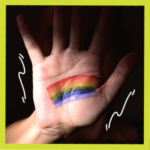 Hand making stop sign with rainbow flag painted on it for LGBTQ ally article