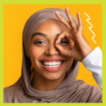 Young woman in head scarf looking through her fingers placed in circle around her eye.