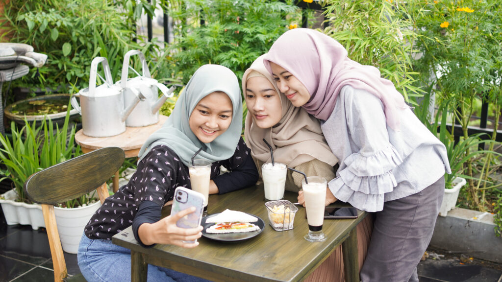 Three girls wearing head veil taking a selfie and smiling