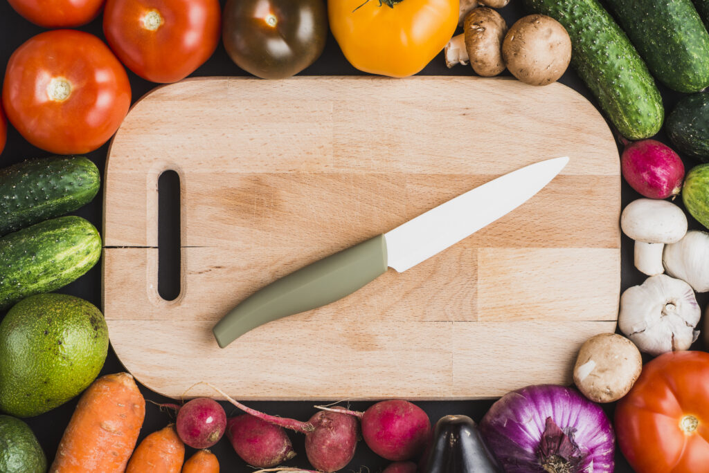 Chopping board, knife and array of vegetables
