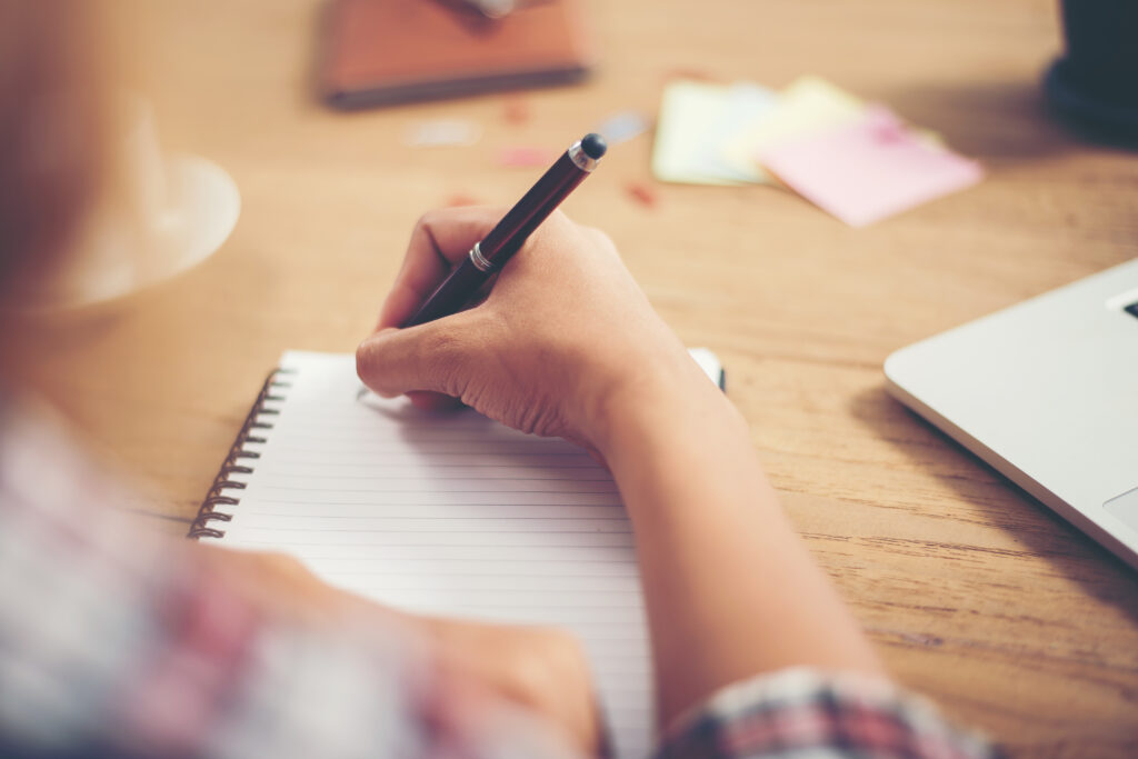 Someone holding pen writing down in book for sad article