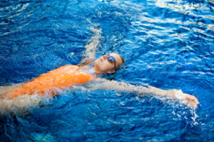 Girl with sunglasses swimming in the pool for water safety article