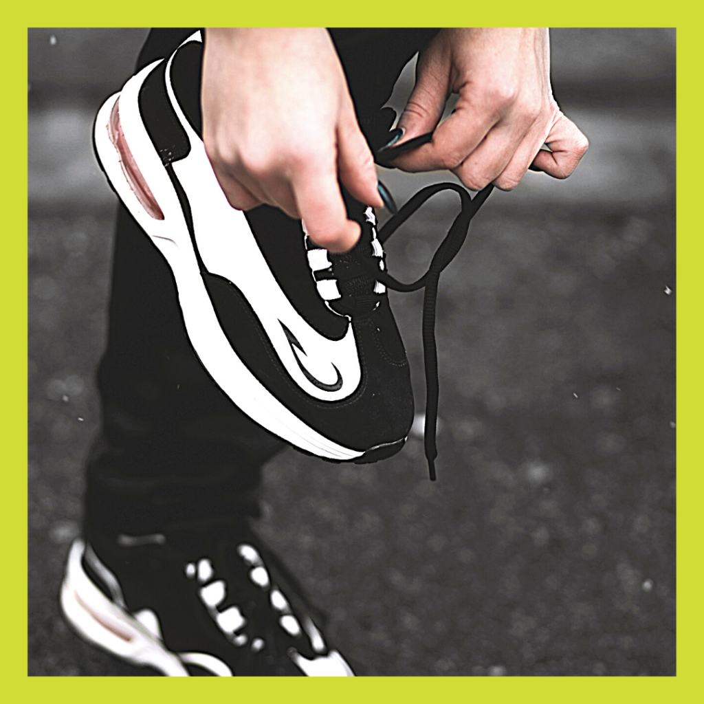 Person tying shoelaces of black and white trainers