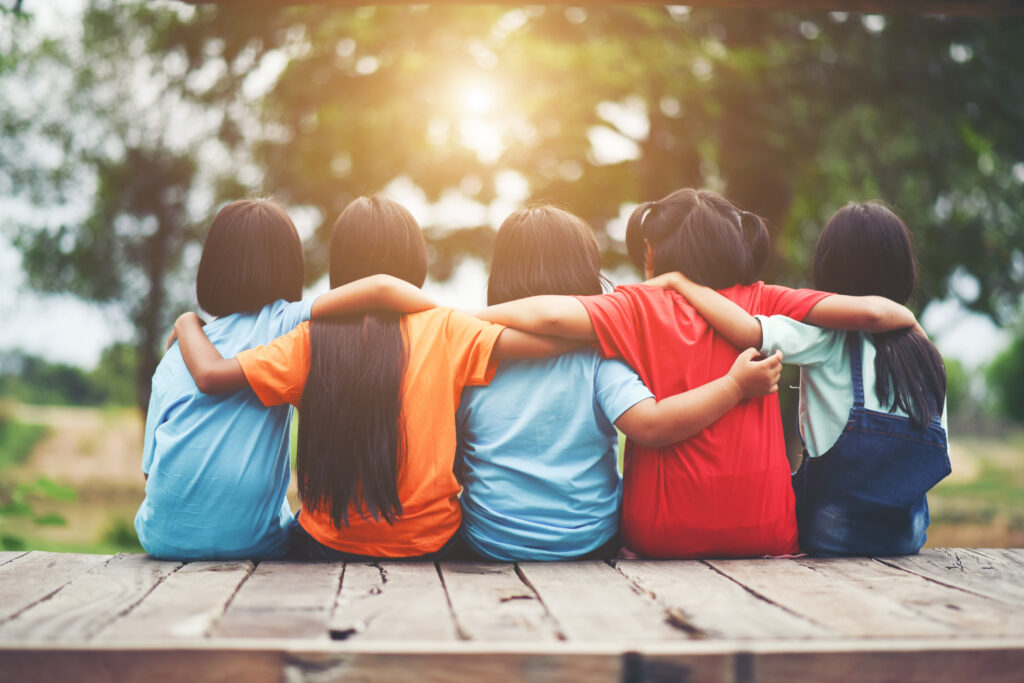 Group of young friends sat down with arms around each other for Survival Guide To Starting Secondary article